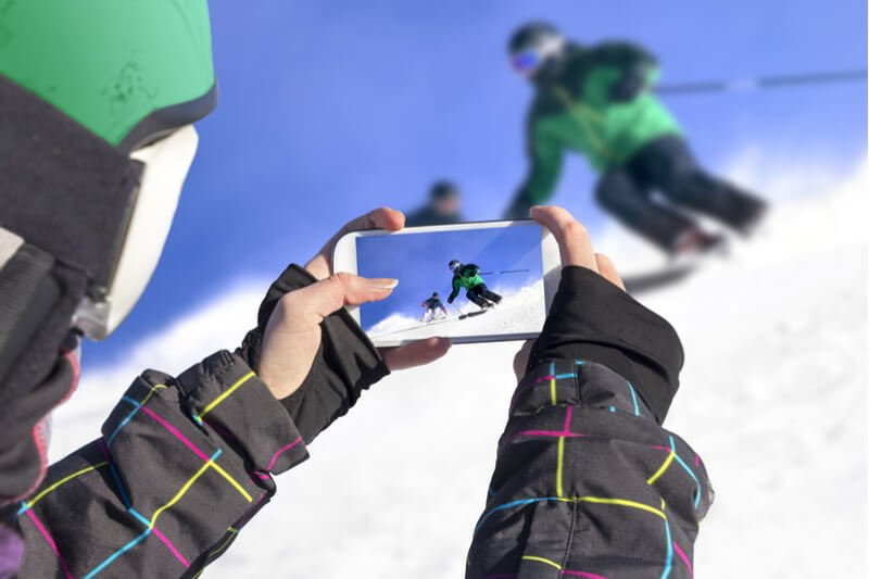 Person filming skiier on their mobile phone