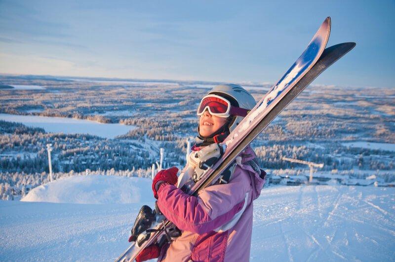 School girl carrying skis