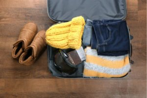 Open suitcase packed for ski holiday