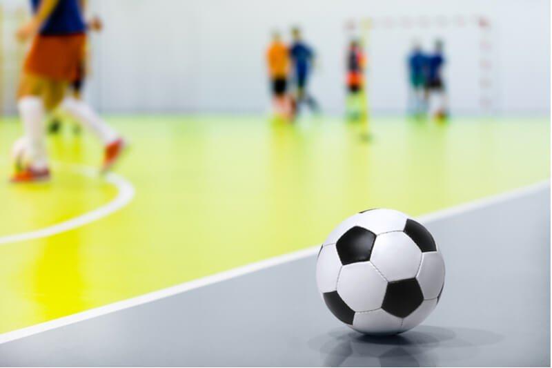 Children playing futsal indoors