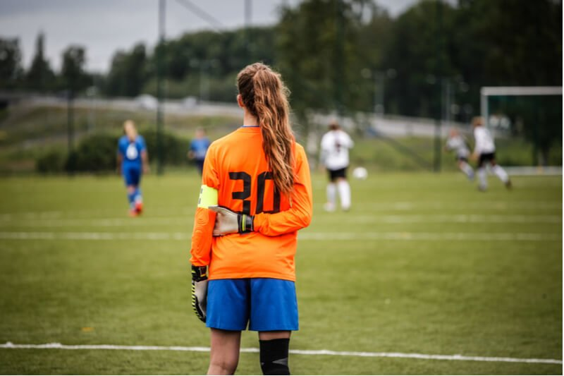 Girl goalkeeper looking at football pitch